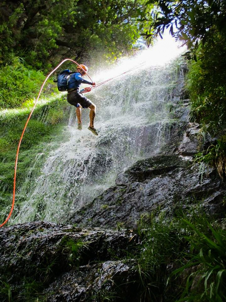Man Abseiling Down Waterfall